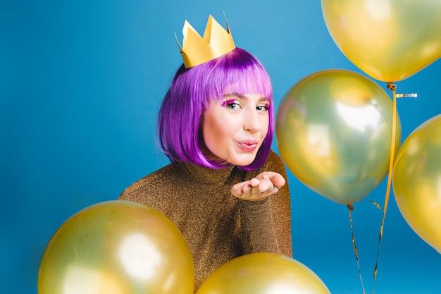 Feliz año nuevo tiempo de fiesta de atractiva joven enviando un beso, rodean globos dorados. cortar el pelo morado, vestido de lujo, divertirse, celebración de cumpleaños. Foto gratis