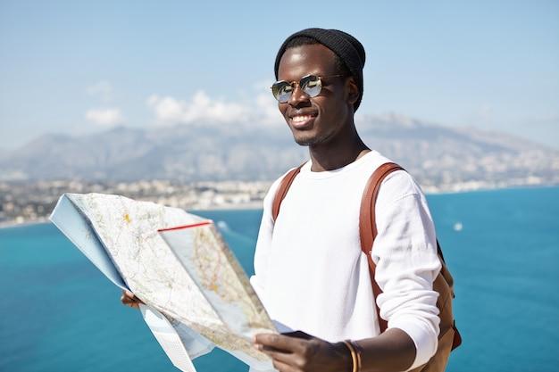 Feliz apuesto joven viajero de piel oscura de pie en la cima de la montaña con un mapa de papel sobre el vasto océano y la ciudad turística, con una mirada alegre mientras viaja por el mundo en compañía de amigos Foto gratis