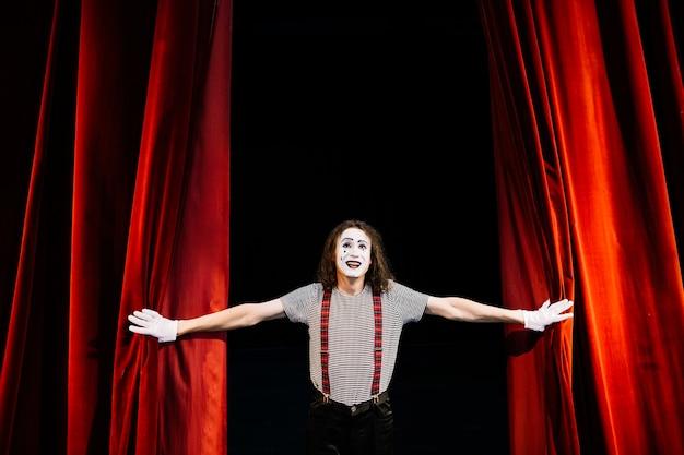 Feliz artista mimo masculino cerca de la cortina roja Foto gratis