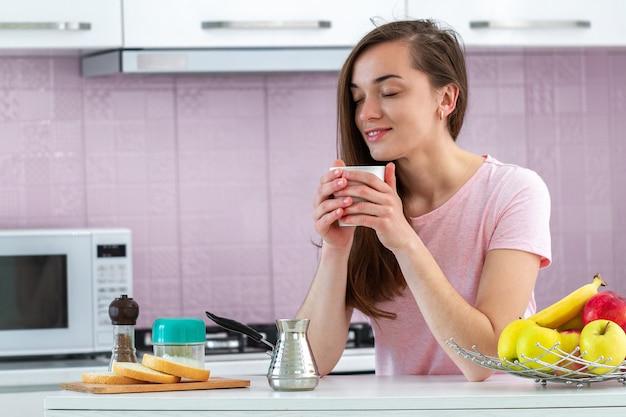 Feliz, atractiva, mujer bebe y disfruta de un café caliente y sabroso para el desayuno temprano en la mañana en la cocina de su casa Foto Premium