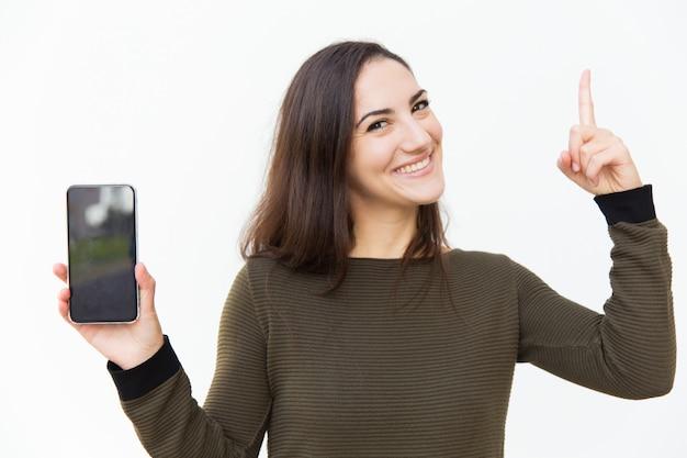 Feliz bella mujer alegre que muestra la pantalla del teléfono inteligente en blanco Foto gratis