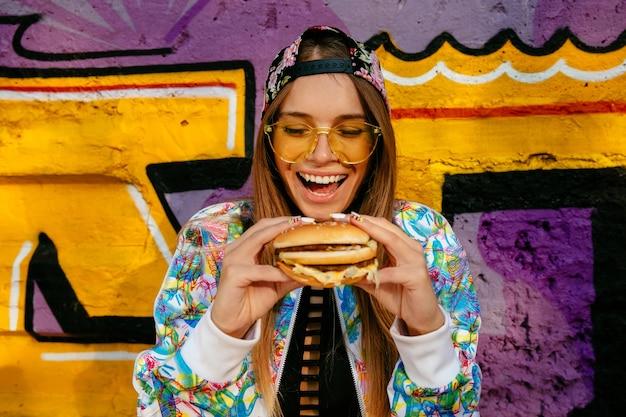 Feliz bella mujer joven, sonriendo ampliamente, tiene sabrosa hamburguesa en dos manos. Foto gratis