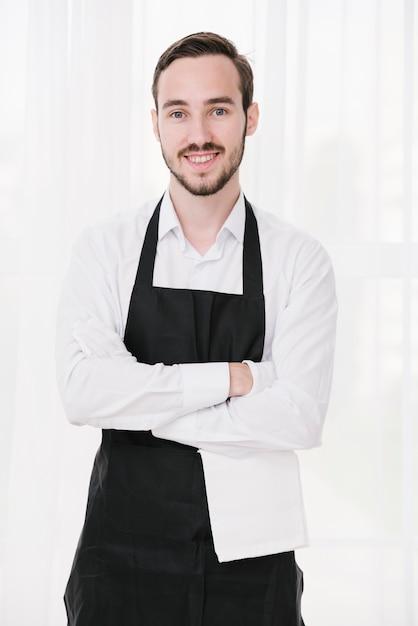 Feliz camarero de pie con las manos cruzadas Foto gratis