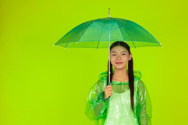Feliz chica hermosa, vistiendo ropa verde, paraguas y abrigo, día lluvioso. Foto gratis