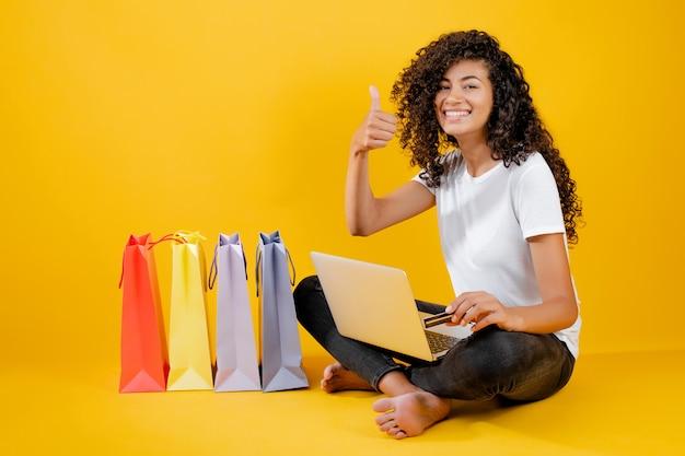 Feliz chica negra con coloridos bolsos de compras sentado con laptop y tarjeta de crédito aislado sobre amarillo Foto Premium