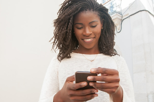 Feliz chica negra enfocada chateando en línea Foto gratis