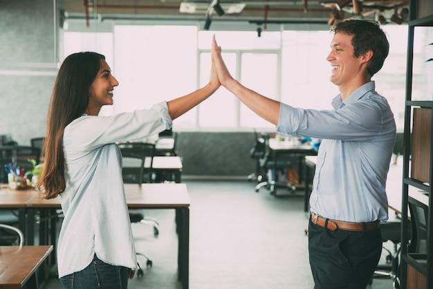 Feliz colegas dando cinco como símbolo de éxito Foto gratis