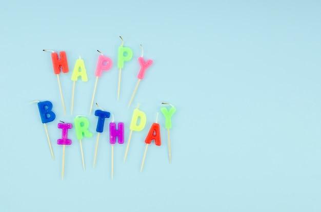 Feliz cumpleaños coloridas velas sobre fondo azul Foto gratis