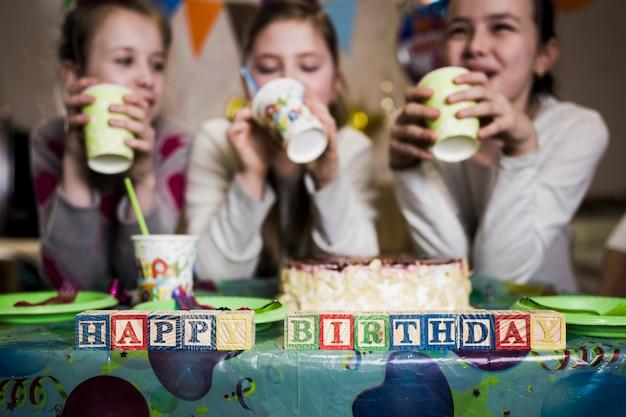 48ce79ebd Feliz cumpleaños escribiendo cerca de chicas bebiendo Foto gratis