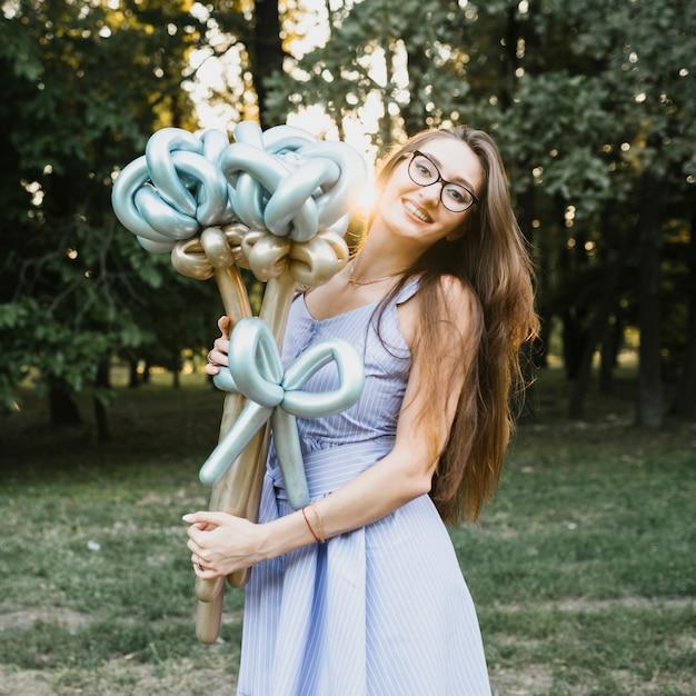 Feliz cumpleaños mujer al aire libre con globos Foto gratis