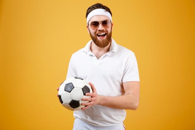 Feliz deportista barbudo con balón de fútbol Foto gratis