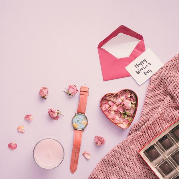 Feliz día de la mujer inscripción con pétalos de rosa y reloj. Foto gratis