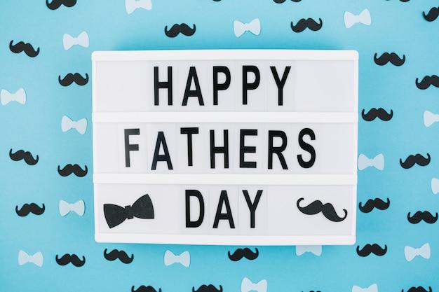 Feliz día del padre título en tableta entre decoraciones Foto gratis