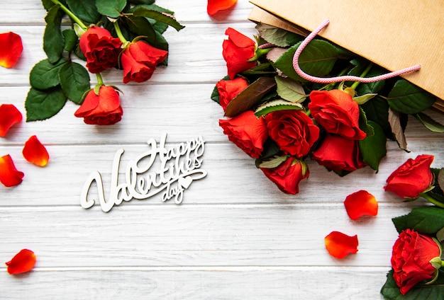 Feliz día de san valentín con rosas rojas y pétalos Foto Premium