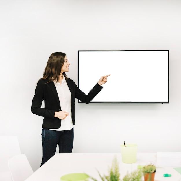 Feliz empresaria apuntando hacia la pantalla en blanco Foto gratis