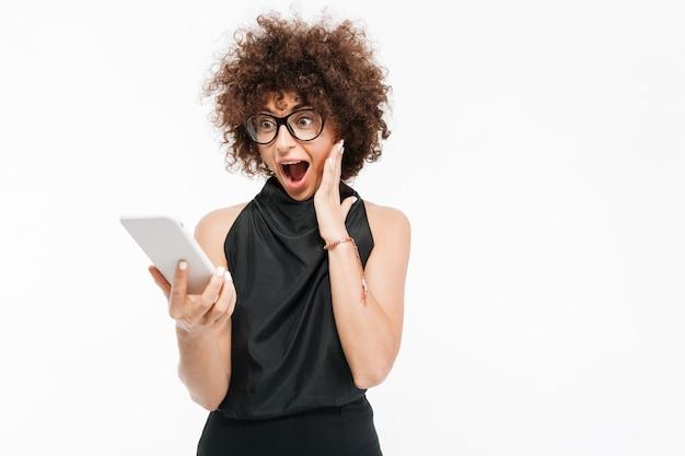 Feliz empresaria emocionada en anteojos mirando tablet pc Foto gratis