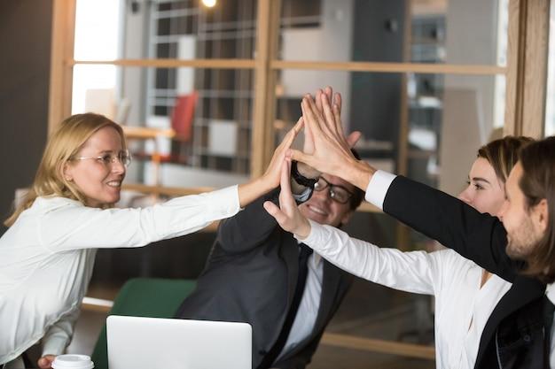 Feliz equipo de negocios que ofrece un alto nivel de compromiso prometedor y lealtad Foto gratis