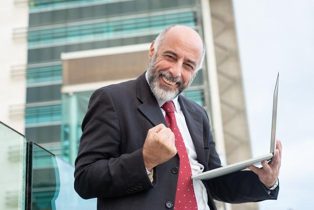 Feliz exitoso líder de negocios maduros con laptop Foto gratis