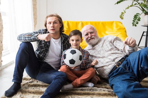 Feliz familia multigeneracional sentados en el piso juntos Foto gratis