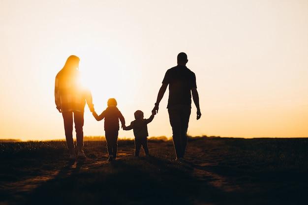 Feliz familia silueta en la puesta del sol Foto gratis