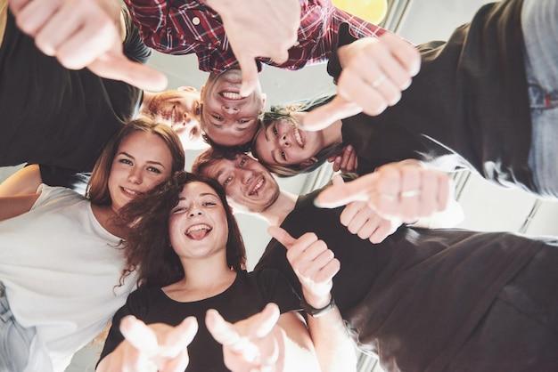 Feliz grupo de amigos con las manos juntas en el medio Foto gratis