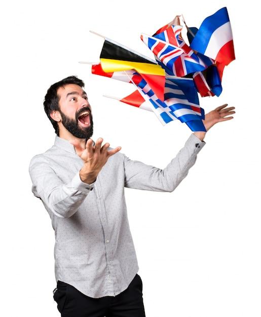 Feliz guapo hombre con barba sosteniendo muchas banderas Foto gratis