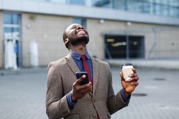 Feliz hombre afroamericano parece suerte leyendo algo en su teléfono inteligente Foto gratis