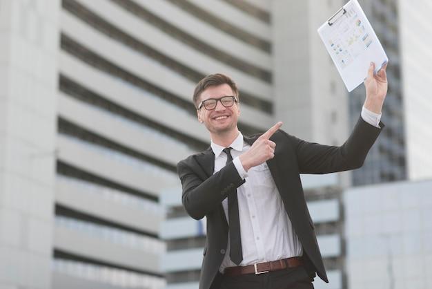 Feliz hombre moderno apuntando al portapapeles Foto gratis