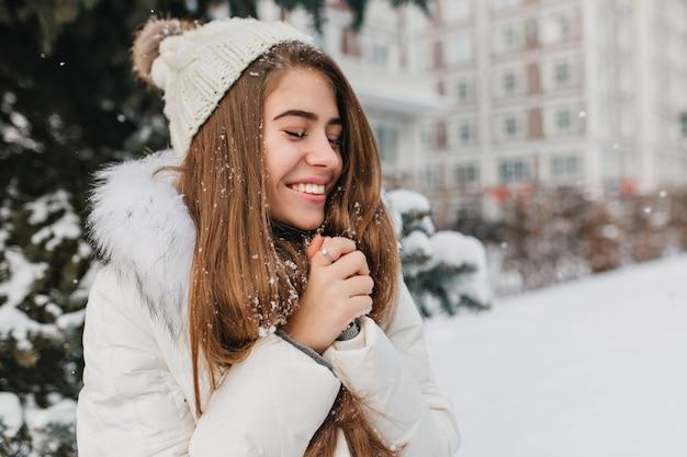 Feliz invierno de la joven mujer alegre disfrutando de la nieve en la ciudad. mujer atractiva, cabello largo morena, sonriendo con los ojos cerrados. Foto gratis