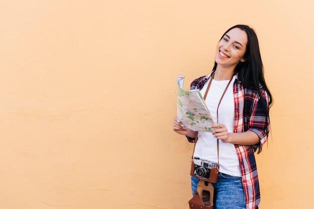 Feliz joven atractiva con cámara y sosteniendo mapa de pie cerca de la pared de durazno Foto gratis