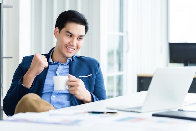 Feliz del joven empresario asiático ve un plan de negocios exitoso en la computadora portátil Foto Premium