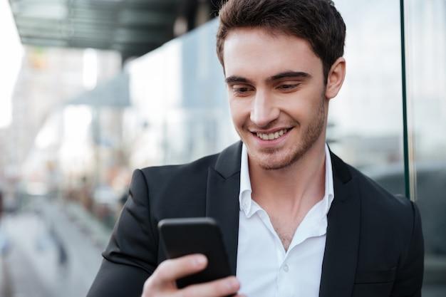 Feliz joven empresario caminando cerca del centro de negocios charlando Foto gratis