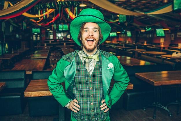 Feliz joven excitado de la mano en las caderas y sonríe a la cámara. lleva el traje de san patricio. guy está solo en el pub. Foto Premium