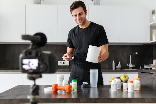 Feliz joven filmando su episodio de video blog Foto gratis