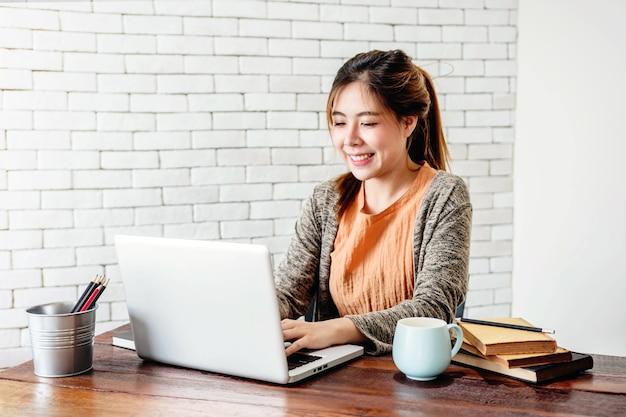 Feliz joven freelancer mujer trabajando en computadora portátil | Foto Premium