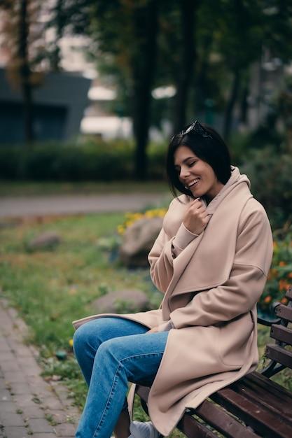 Feliz joven morena sentada en un banco del parque Foto gratis
