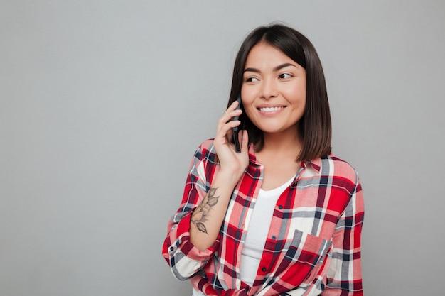 Feliz joven mujer asiática aislada sobre pared gris Foto gratis