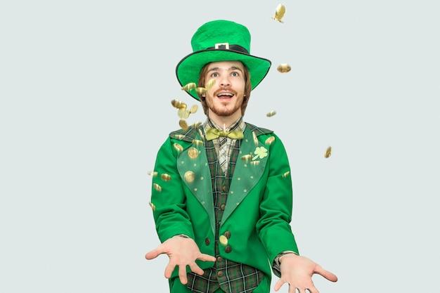 Feliz joven rico en traje de san patricio extendiendo monedas de oro y sonriendo. ellos vuelan. guy mira hacia arriba. aislado en gris Foto Premium