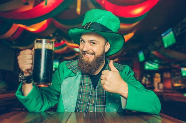 Feliz joven sentado a la mesa en el pub y pose. sostiene una jarra de cerveza oscura. guy se ve feliz. lleva el traje de san patricio. Foto Premium