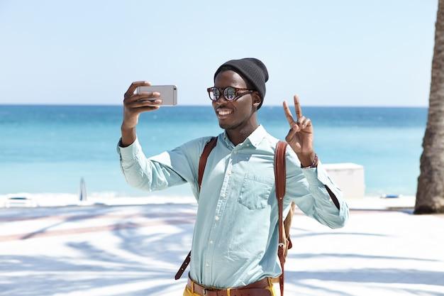 Feliz joven viajero masculino con mochila mirando y sonriendo a la cámara en su teléfono inteligente Foto gratis