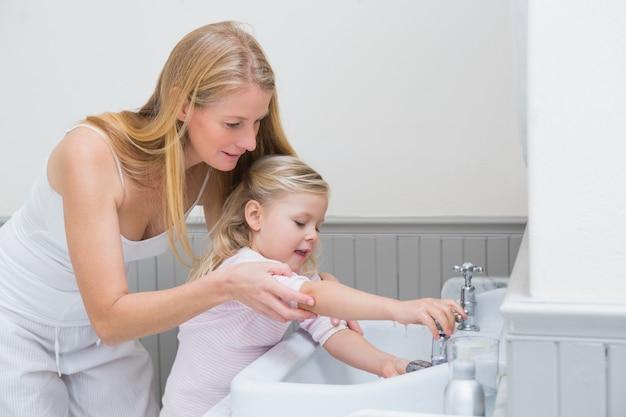 Feliz madre e hija lavándose las manos Foto Premium