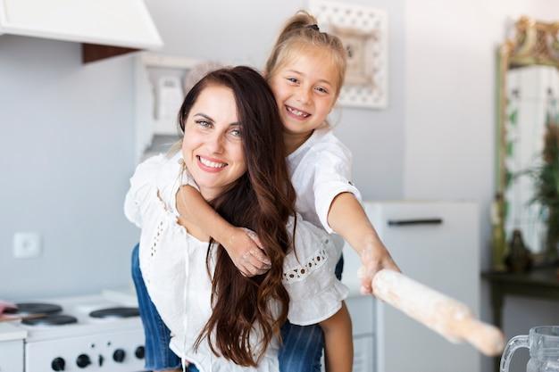 Feliz madre e hija posando con rodillo de cocina Foto gratis