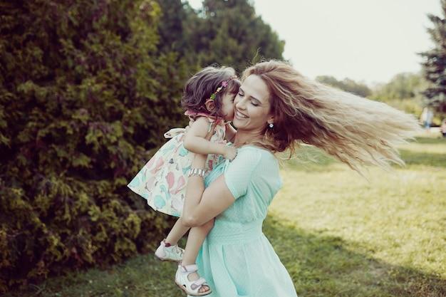 Feliz madre e hija riendo juntos al aire libre Foto gratis