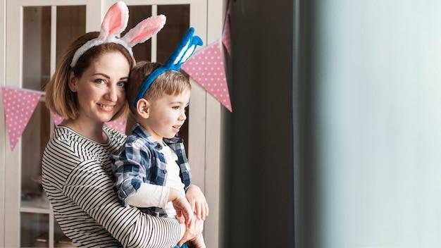 Feliz madre con niño con orejas de conejo Foto gratis