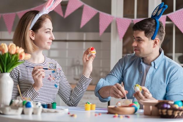 Feliz madre y padre pintando huevos juntos Foto gratis