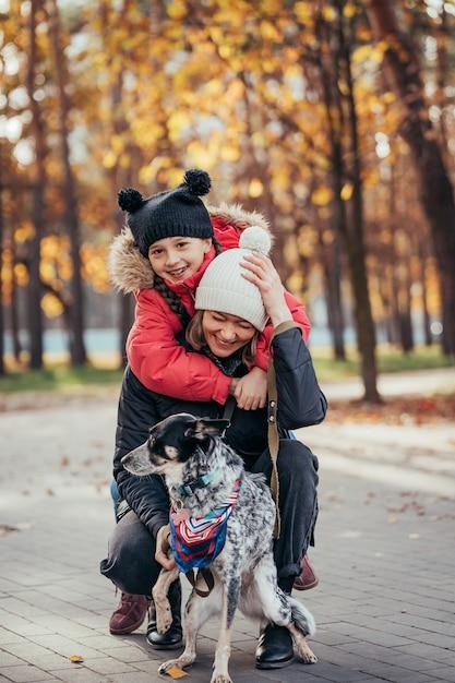 Feliz madre y su hija jugando con perro en el parque otoño Foto gratis