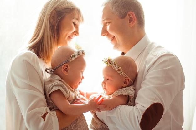 Feliz mamá y papá posan con divertidos gemelos en sus brazos ante una ventana brillante Foto gratis