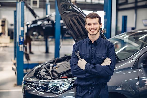 Feliz mecánico de pie junto al auto Foto Premium