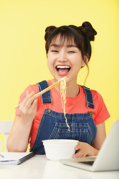 Feliz mujer asiática llevando fideos instantáneos con palillos a la boca, frente a la computadora portátil Foto gratis