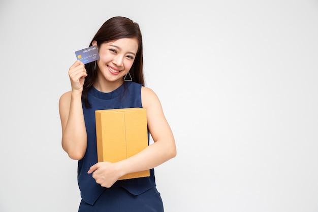 Feliz mujer asiática con paquete paquete caja y tarjeta de crédito, servicio de envío de entrega y compras en línea concepto Foto Premium